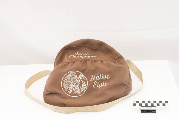 Brown drum bag with a design and lettering on front